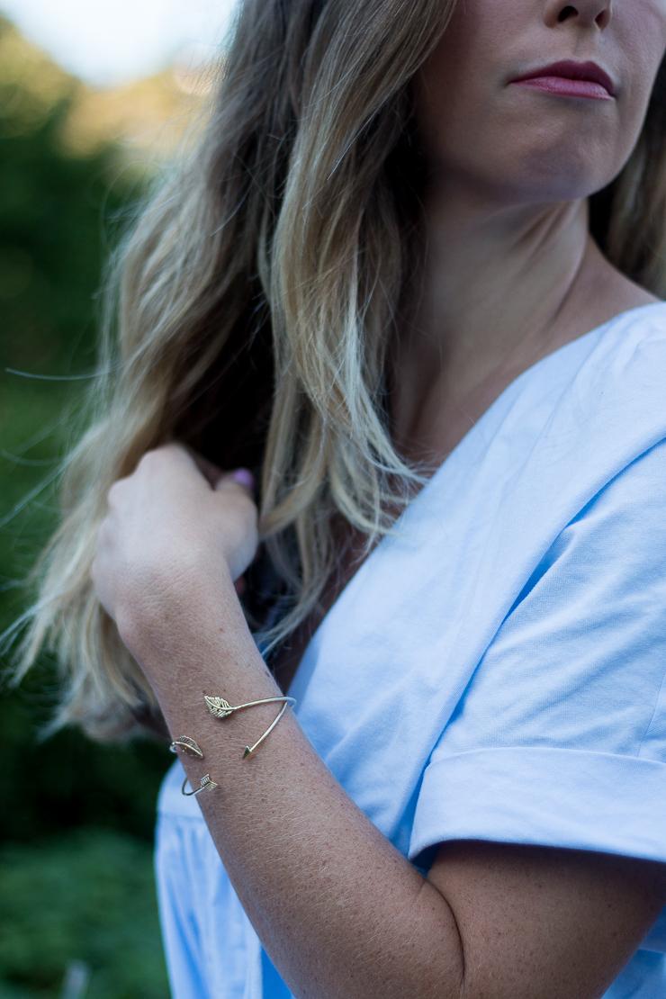 gold bracelets against blue dress