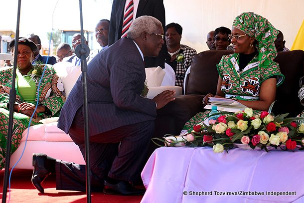 Local government minister Ignatius Chombo kneels at First Lady Grace Mugabe's feet at a ceremony held for the beneficiaries of a housing scheme in Kadoma.