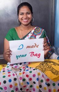 """Une femme souriante en sari tient un écriteau où il est écrit """"I made your bag"""""""