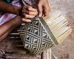 Un artisan en Indonésie est en train de tisser un panier batak