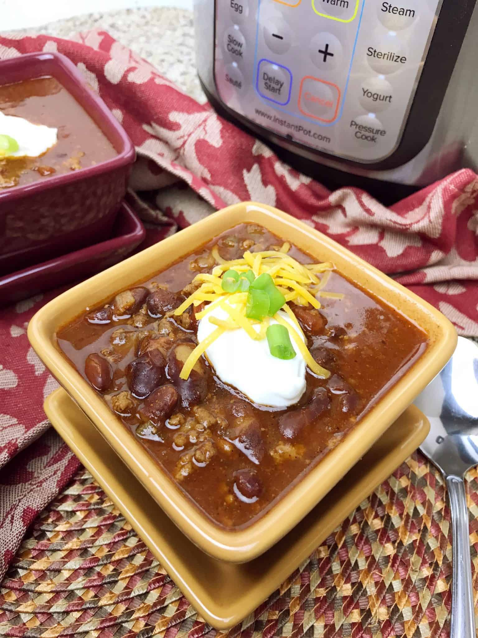 Instant Pot Chili is so delicious with a dollop of sour cream, cheese, and onions.