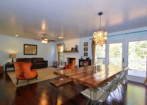 open living and dining with view of painted white brick fireplace and farmhouse table renovated space