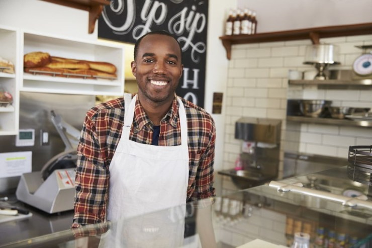 Business owner behind the counter at a sandwich bar