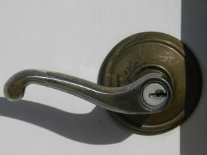 A lever-style doorknob where the user has a long metal handle that sticks back toward the door to push down and either pull or push against to open the door.