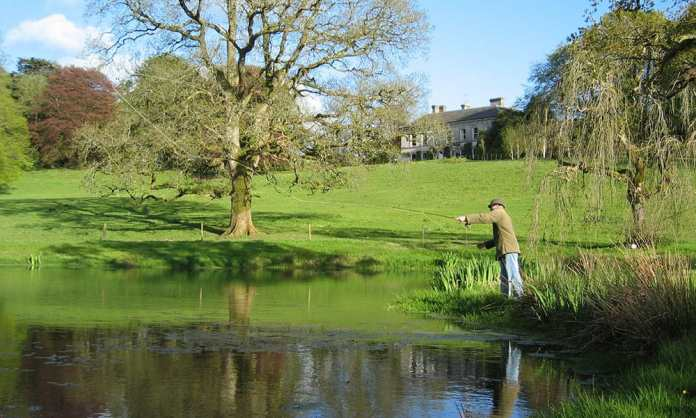A Fly Fisherman casting his line on one of the lakes in the grounds of Ballyvolane House, Co. Cork - The Irish Place
