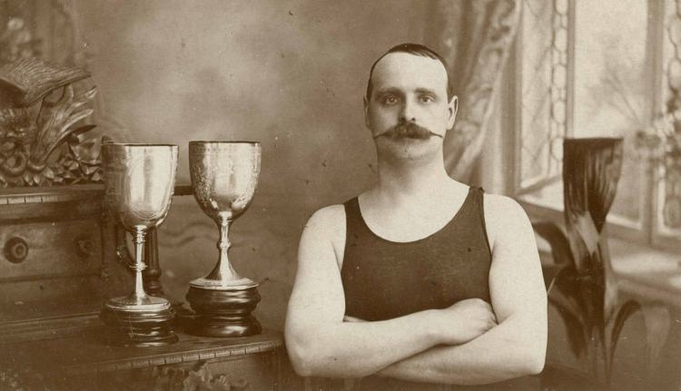 Man in a swimming costume standing with two trophies