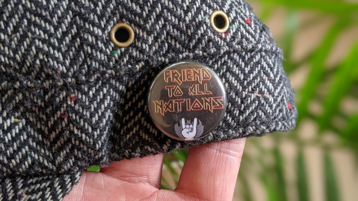 Image of a button badge reading 'Friend to all nations' in an iron maiden font