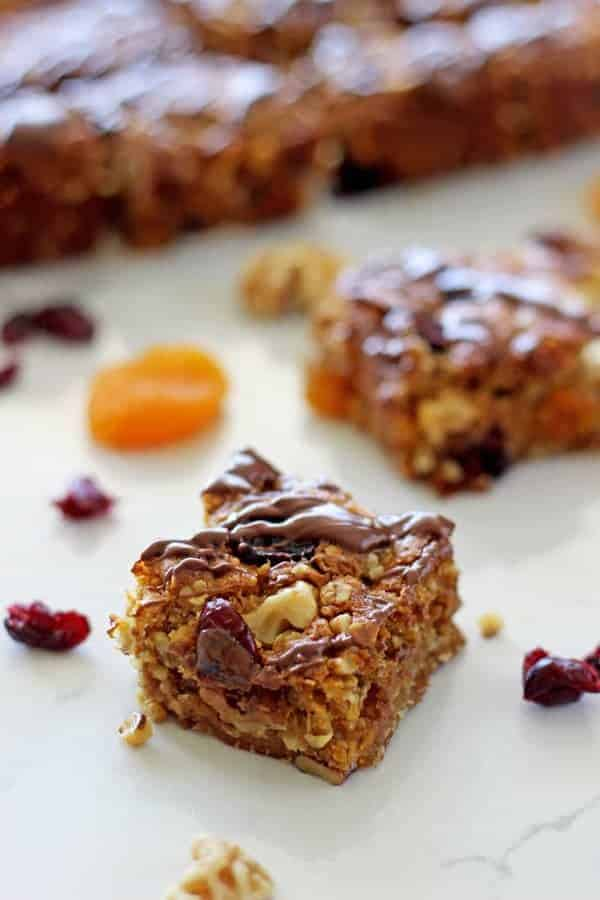 This loaded Anzac slice recipe is a twist on the traditional Anzac biscuits, filled with cranberries, apricot, walnuts and topped with a chocolate drizzle!