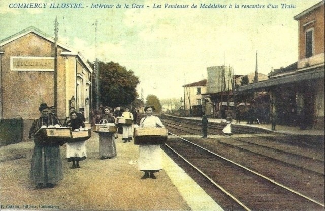 Women standing next to train station selling madeleines in Commercy.