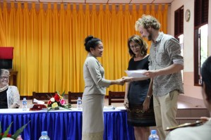 "Mittaphone ""Mit"" Sichampa (English teacher at Sikeud primary school) receives her certificate from Johannes Zeck & Prof. Marti (""John & Izzy"")"
