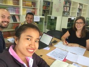 David Schrep, Ms Khantanaly Panvilaysone, Mr Kaikeo Phothichak, and Jasmin Unterweger in the library at SKU
