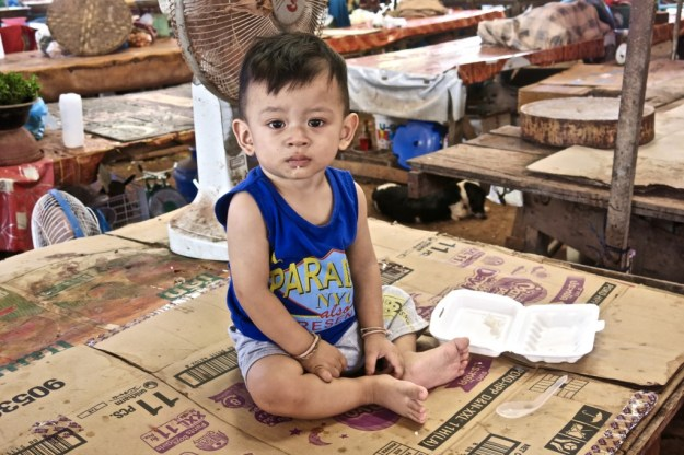 Toddler on empty market stall, Ban Sikeud