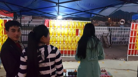 Khamsee and Phonechit at a night market stand, where you use dart pins to burst the balloons in order to win.