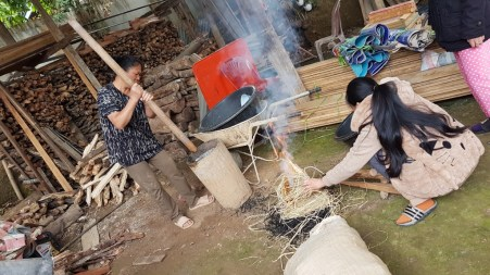 Aunt Thay mixes the ash of the rice leaves with the uncooked sticky rice in the mortar while Khamsee burns more rice leaves.