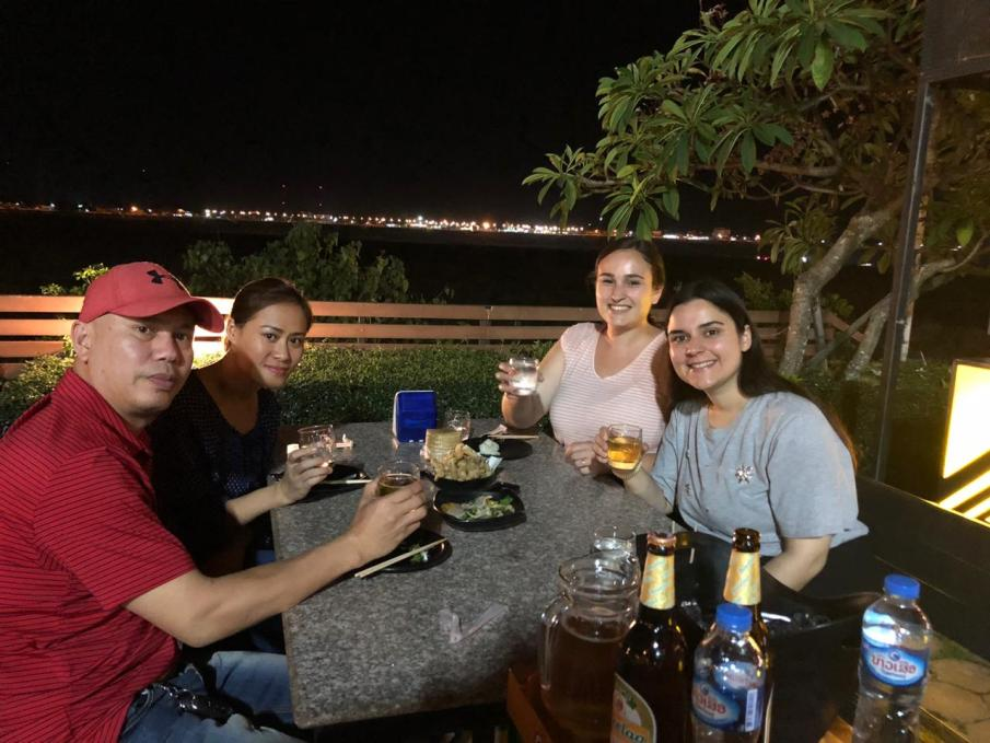 Taa, Dit, Jacqui, and Laura have farewell-drinks at the Mekong riverside