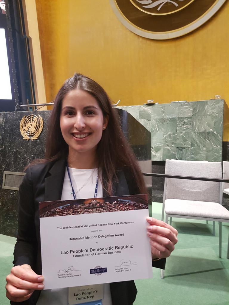 Shirin Ud-Din holding an award for her delegation