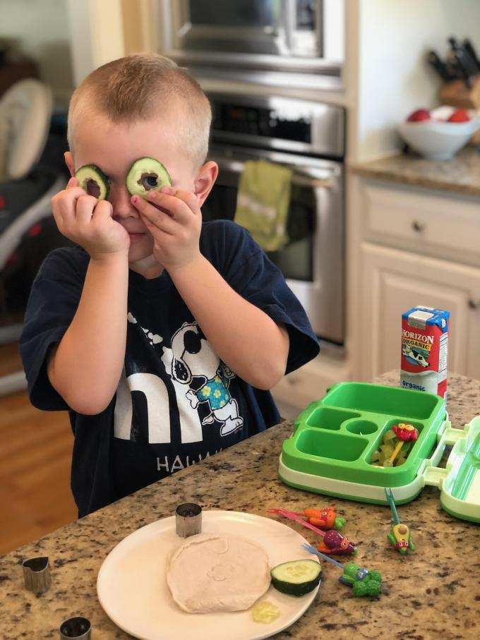 boy holding cucumber cut outs over eyes like glasses while doing school lunch packing