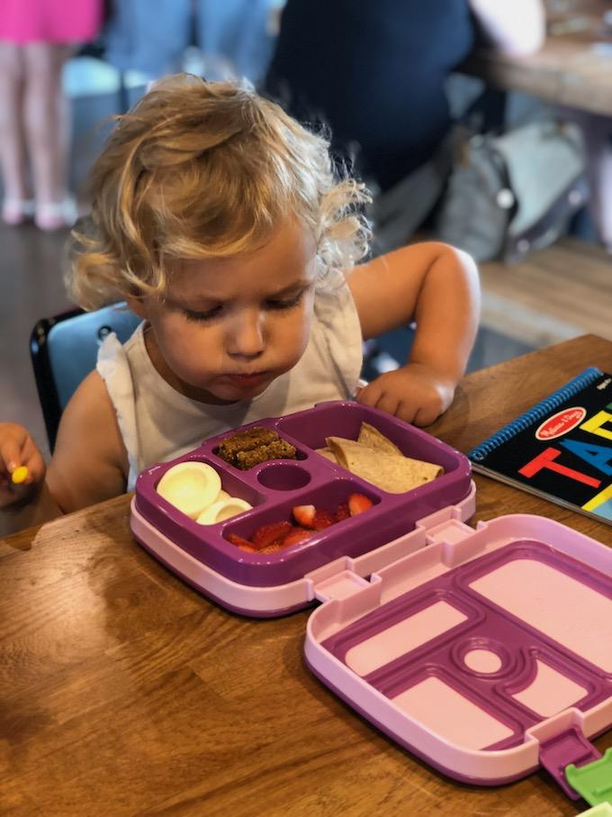 toddler eating quesadilla and hard boiled egg out of lunch box