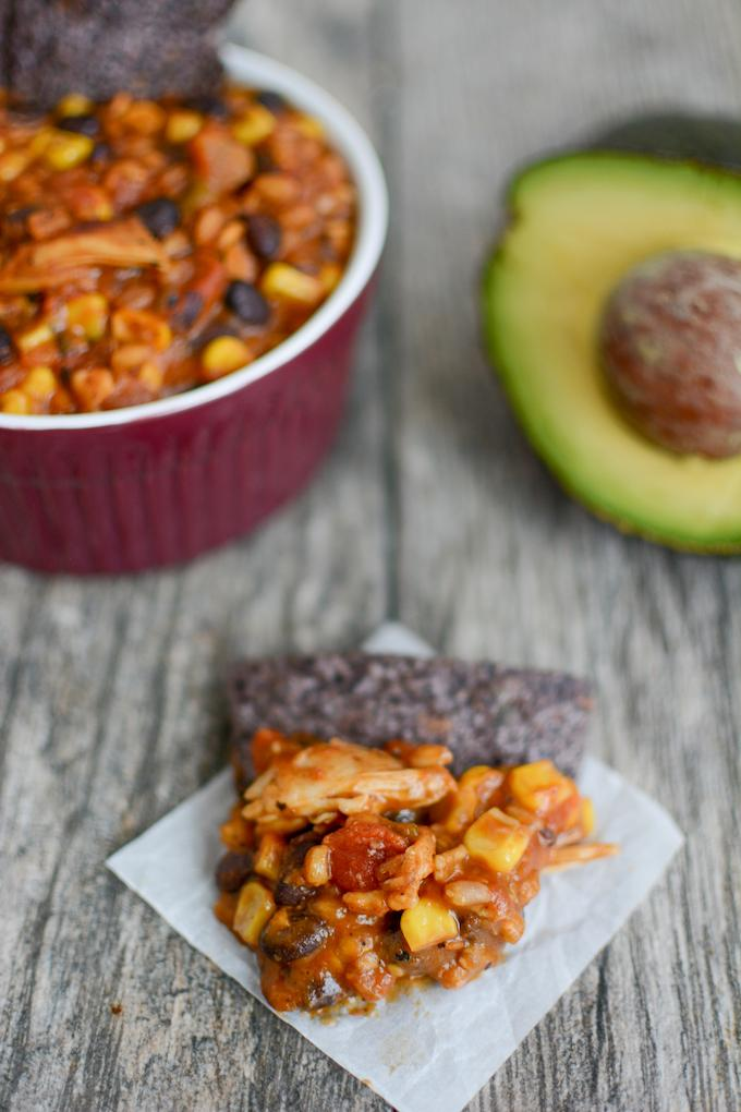 Instant Pot Farro Enchilada Casserole scooped with tortilla chip