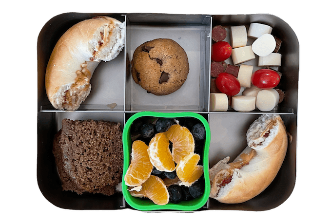 kids lunch box with peanut butter and jelly bagel, fruit salad, banana bread and cookie