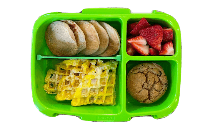 breakfast for lunch box with pancakes, egg waffle, banana carrot muffin and strawberries