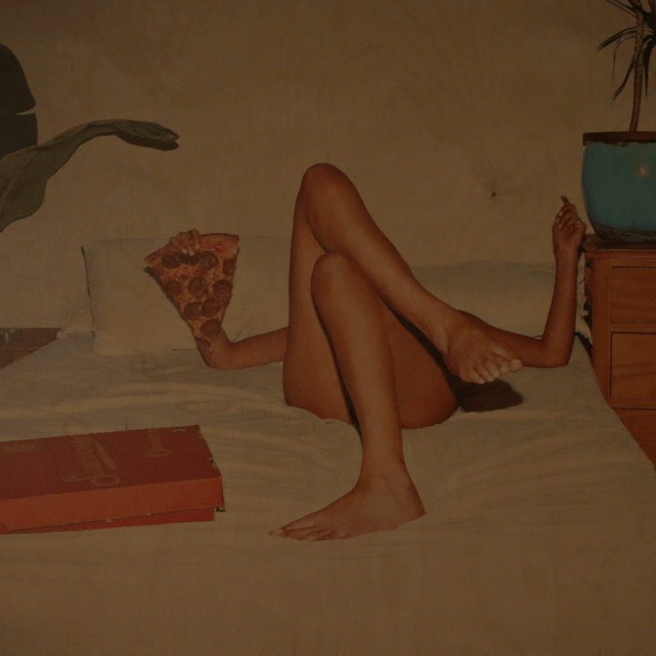This is a picture of a famous piece of art by Sarah Bahbah called Sex and Take Out. A woman lies naked in bed holding a large slice of pizza.