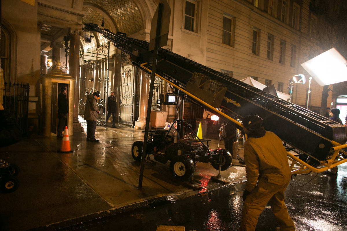 "A booming shot that soars over the wrought iron gates of the ""Dakota"" set is tested on the technocrane."