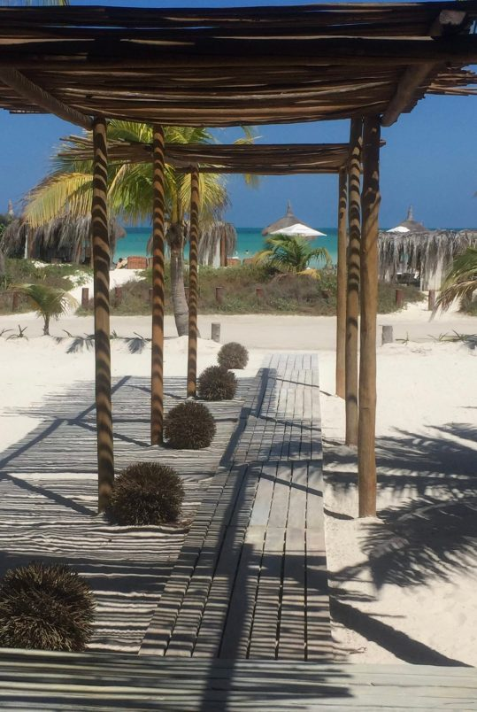 photo of palapa on white sand beach and beach umbrellas before turquoise ocean water of la isla bonita holbox mexico
