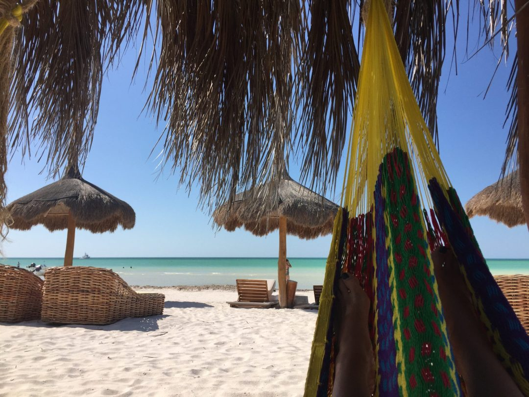 photo of white sand beach planted with palm frond umbrellas before turquoise ocean water of la isla bonita holbox mexico
