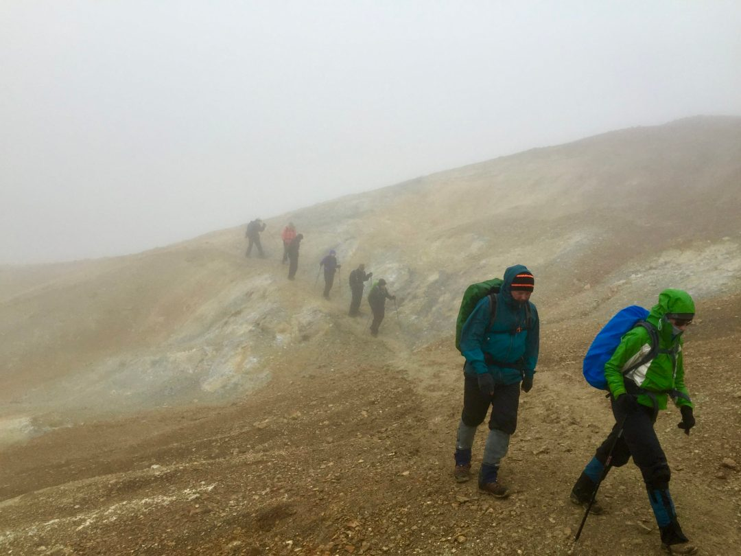 photo of seven mountain hikers carrying packs in a line on a misty trail