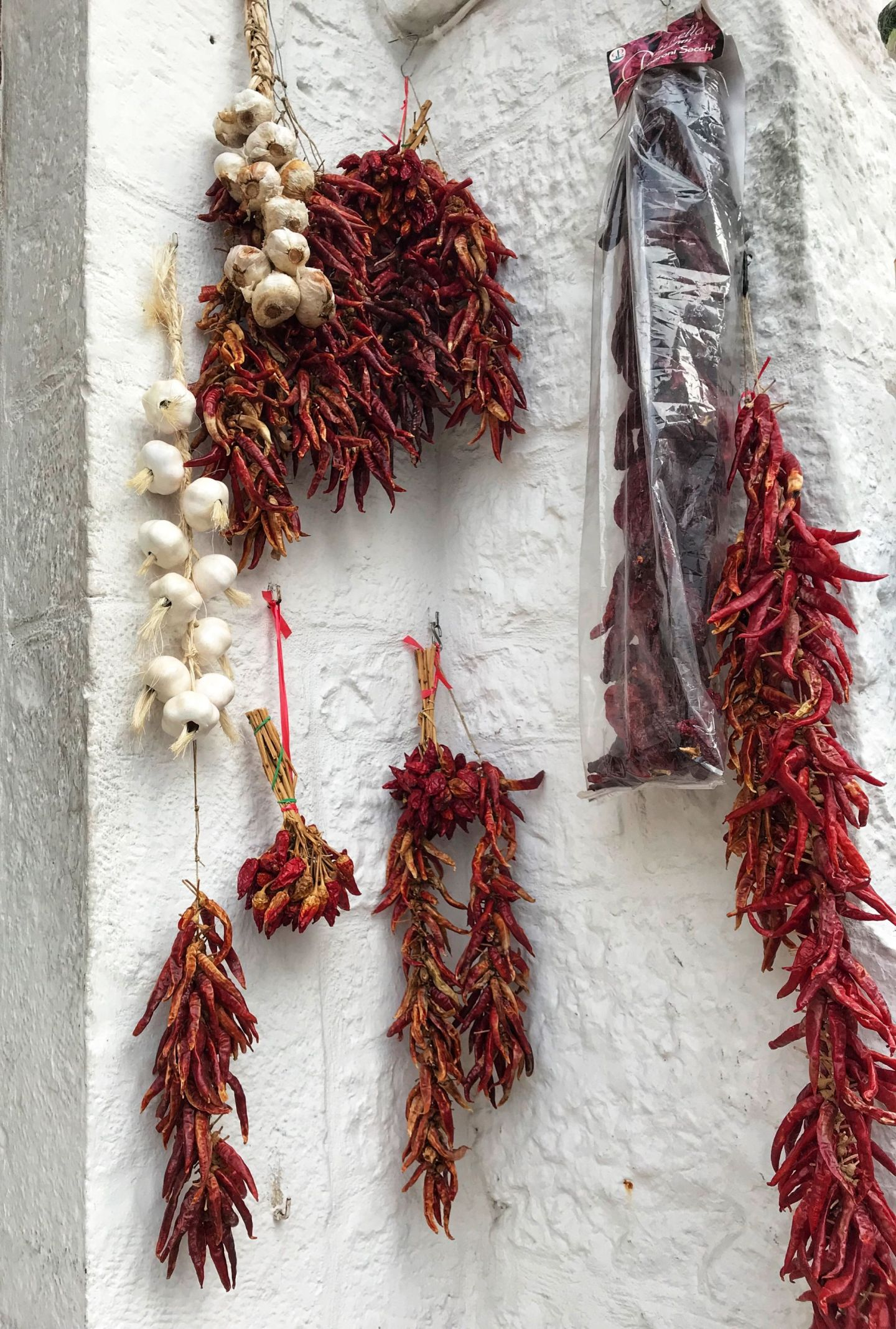 Chillis and garlic hanging from the walls in Alberobello