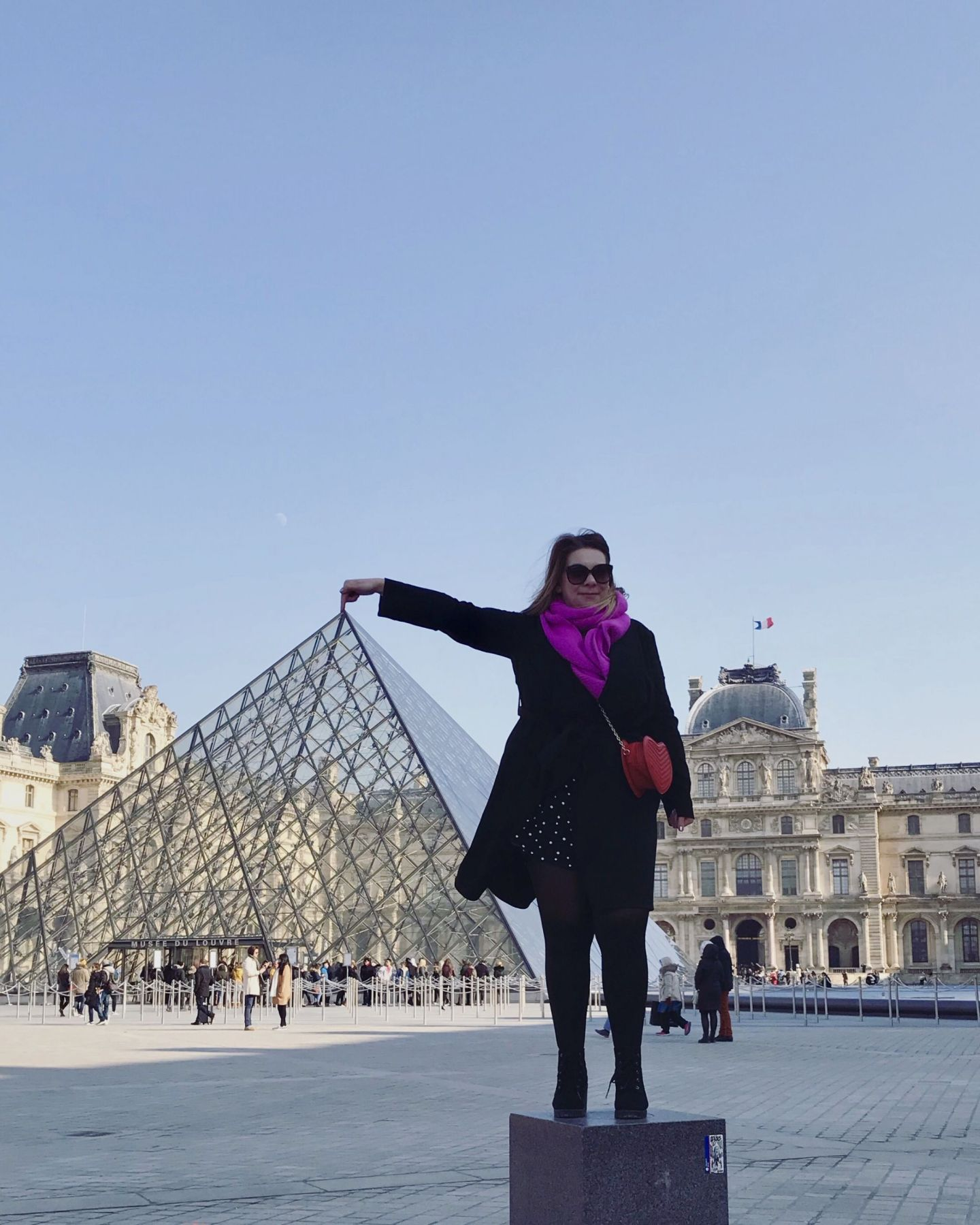 Touching the pyramid point at The Louvre Paris