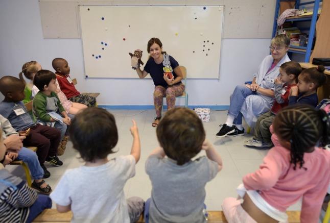 A teacher leading a class of children.