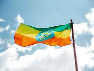 national colorful flag of ethiopia under cloudy sky