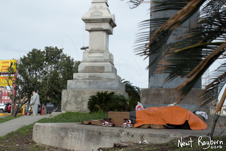 "A homeless person sleeps under The Battle of Liberty Place monument in New Orleans, Louisiana, January 2, 2016. Photograph © 2016 Newt Rayburn - newtrayburn@gmail.com. Cardboard sign reads ""NEED A BLESSING ANYTHING HELP"""