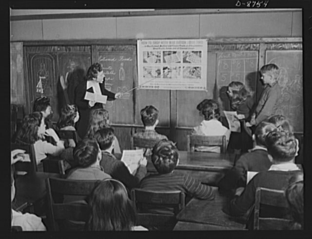 Preparation for point rationing. Catherine M. Rooney, 6th grade teacher at the Murch Elementary School, Washington, D.C., explains to her interested pupils how to use war ration book two when shopping for processed foods.  Public domain.