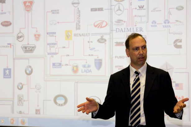 Event-photo-giving-lecture-in-front-of-logos