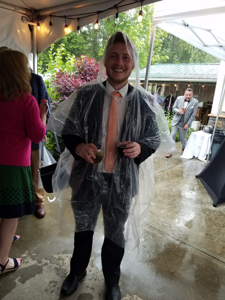 guest in a poncho rainy wedding in the pacific northwest at The Lookout Lodge in Snohomish