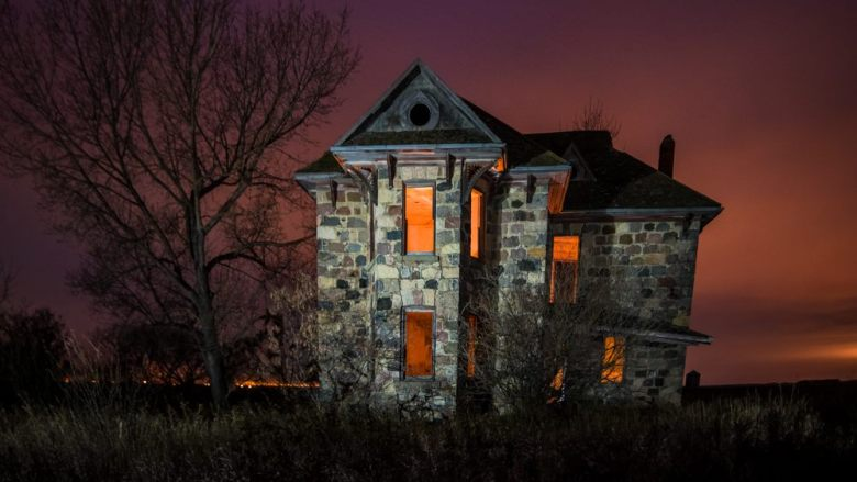 An abandoned stone house with orange-lit windows on a cloudy night.