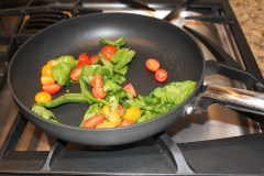 sauteeing the tomatoes, spinach, and basil