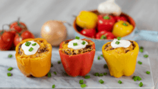 orange red yellow pepper stuffed with homemade chili with sour cream cheese green onions marble background peppers in background in bowl