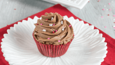 brownie cupcake in red liner on white flower plate topped with chocolate frosting and sprinkled with hearts