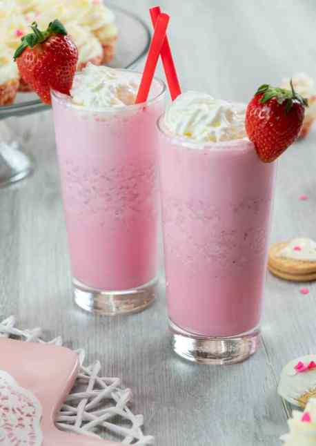 strawberry ice cream milkshake with whipped cream and fresh strawberry garnish chocolate dipped cookies and heart chocolates pink and white sprinkles