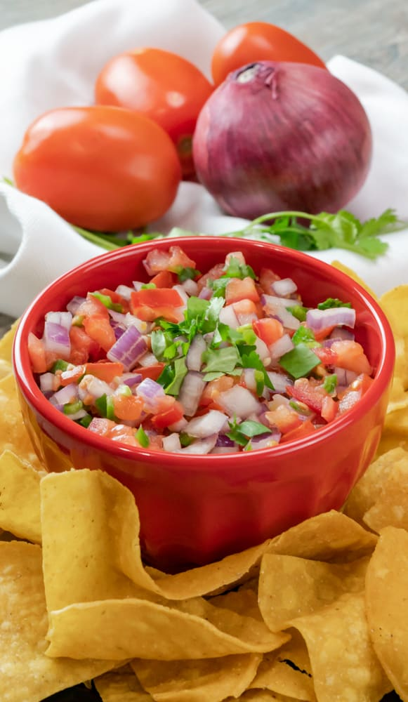 fresh pico de gallo with fresh baked tortilla chips and gray background