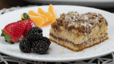 sour cream coffee cake served with blackberries strawberries and mandarin oranges. Served on a white plate