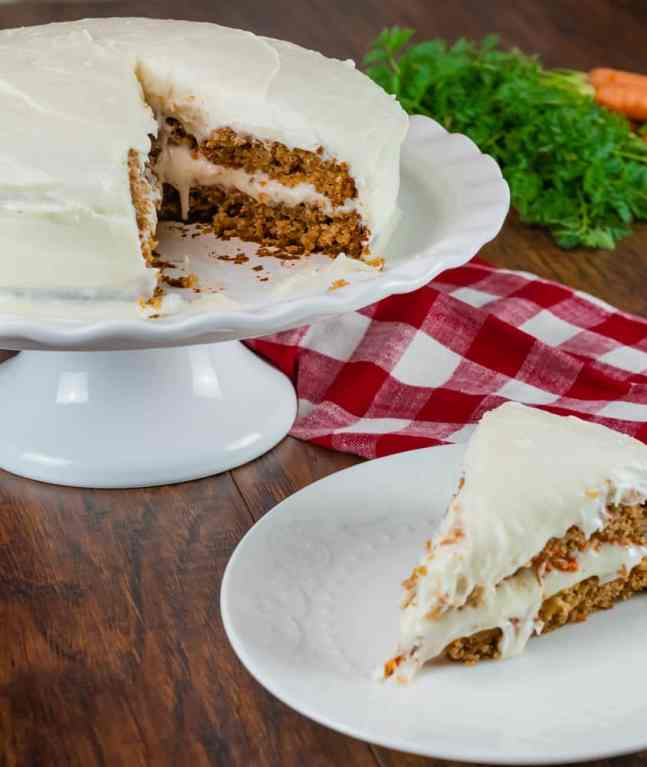 round carrot cake with cream cheese frosting with slice taken out of it and sitting on white plate with red and white napkin