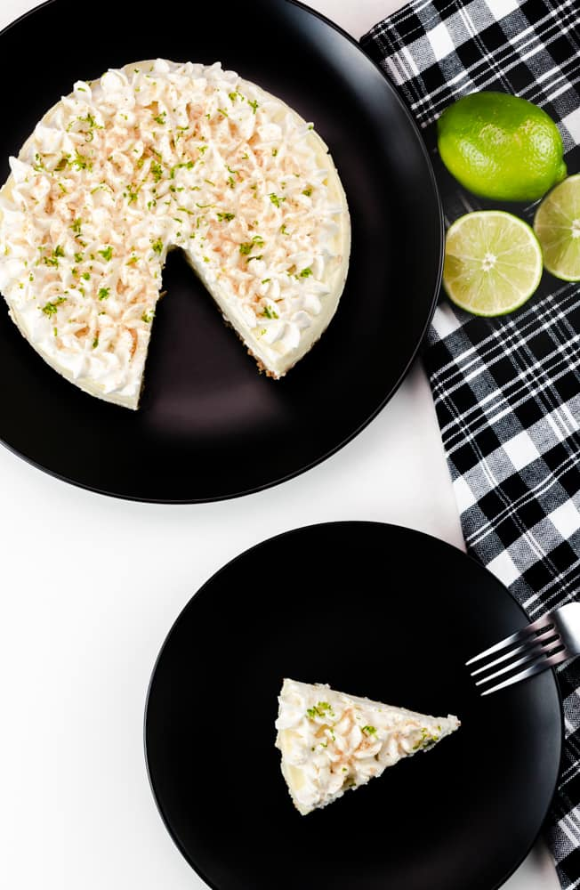Instant Pot Key Lime Cheesecake with homemade whipped cream, crushed graham crackers and lime zest on black plate