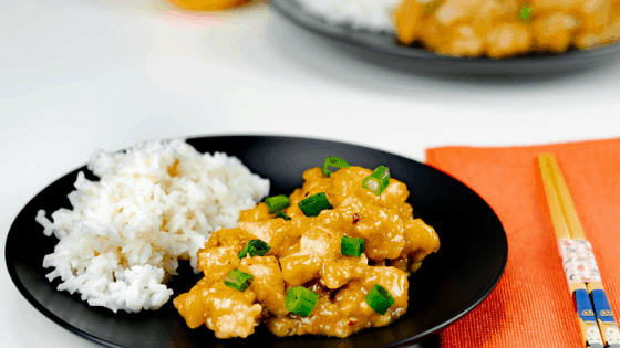 Instant Pot Panda Express Orange Chicken Copycat with white rice on black plate with orange napkin and chopsticks