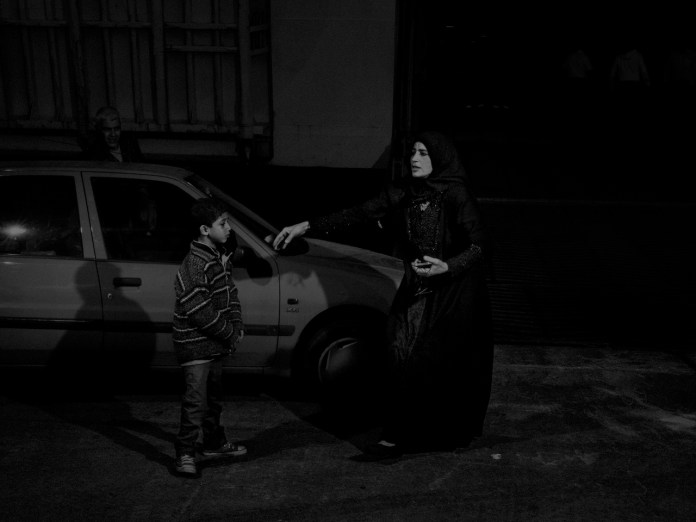 Greece. 2015. A syrian refugee woman desperately searching for her two year old child which she lost on the journey to Pireus from Lesbos. While I was photographing the refugees coming into the port, I noticed this woman who was desperately searching for her lost child and was surprised to see her leave without having found her. She was faced with a hard decision: choosing to leave a child behind and carry on her journey for her other children's sake or lose the bus that would take her to the next checkpoint of her journey.