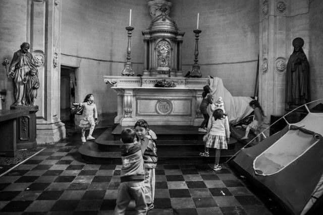 Bambini rifugiati afghani giocano nell'abside della chiesa occupata di Saint J. B. au Béguinage a Bruxelles, nella quale vivono da qualche settimana. © Alberto Campi